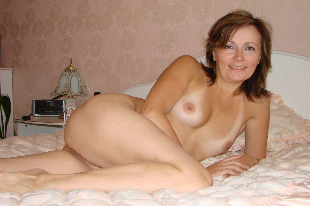 Dojrzała kobieta nago kusi sexy ciałkiem w sypialni. Goła dojrzała amatorka pozuje erotycznie na łóżku