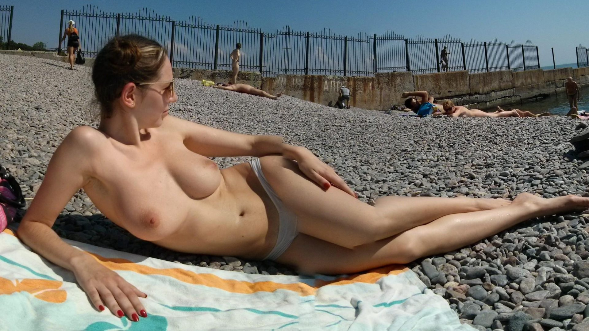 Nago amatorka opala cycki na plaży. Dziewczyna toples relaksuje się zażywając kąpieli słonecznej