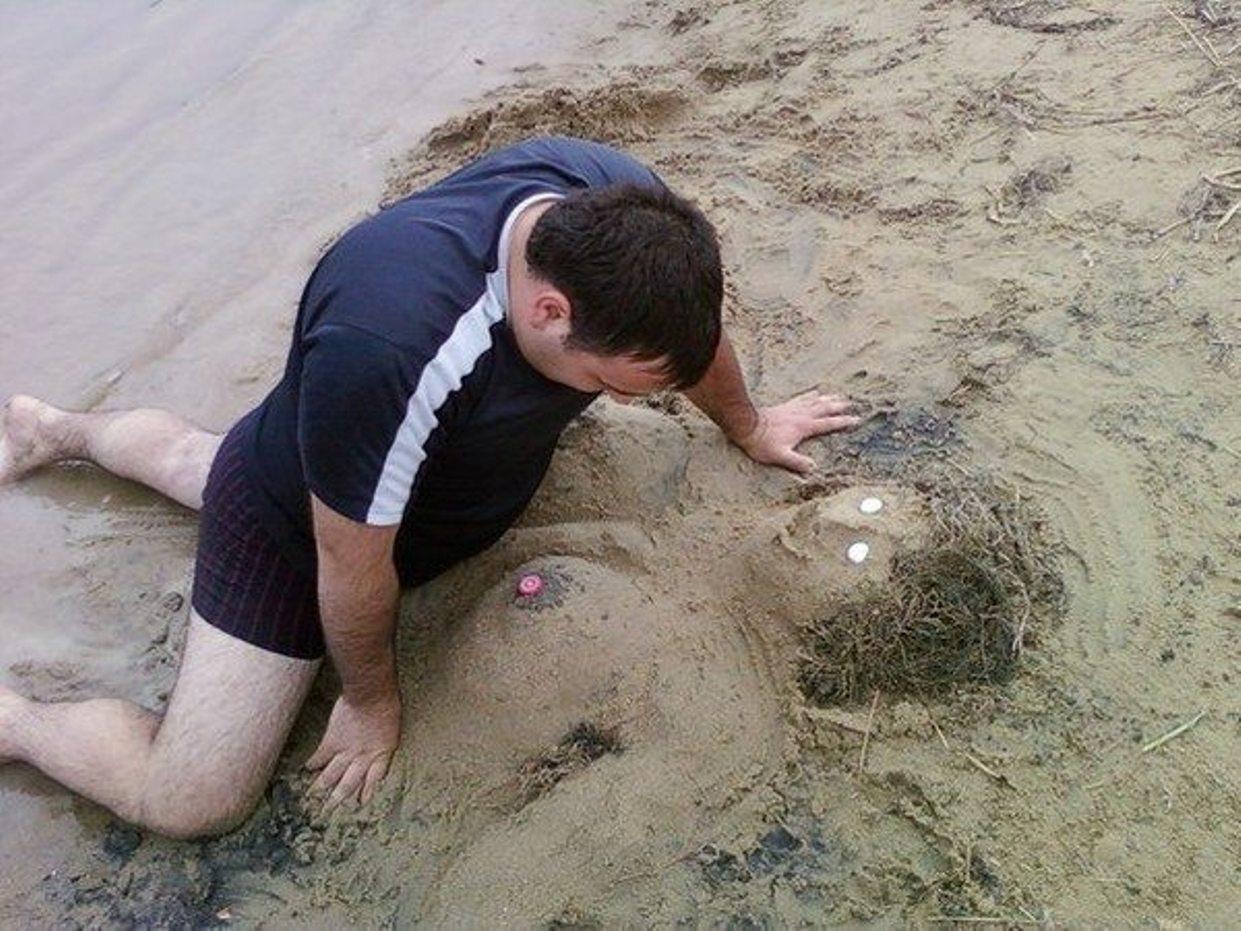 Facet zabawie się na plaży z ulepioną z pisku babką. Jak się nie ma co się lubi to się lubi co się ma