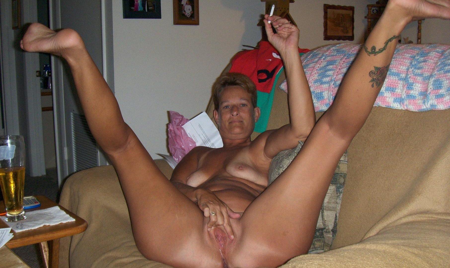 Stara babcia goła pali papierosa. Staruszka nago prezentuje erotyczne wdzięki niezwykle odważnie