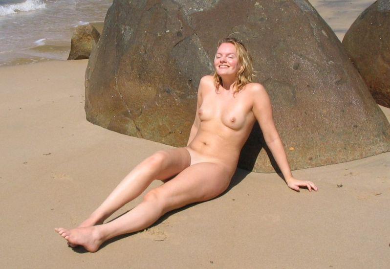 Naga Dunka łapie promienie słoneczne leżąc na piasku